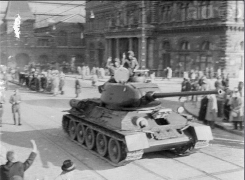 Original caption Hungarian Army crewmen wave to passersby from the turret of their tank in a Budapest street.